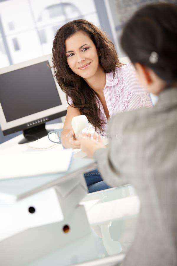 Όμορφο κορίτσι που περνά το τηλέφωνο στο συνάδελφο στην αρχή στοκ φωτογραφία με δικαίωμα ελεύθερης χρήσης