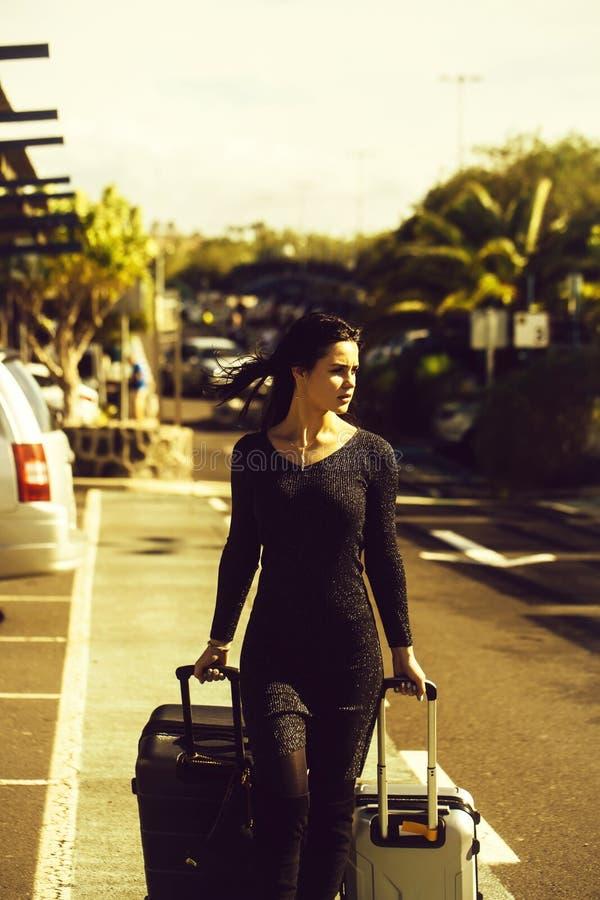 Όμορφο κορίτσι που περπατά και που κυλά δύο βαλίτσες στοκ εικόνες με δικαίωμα ελεύθερης χρήσης