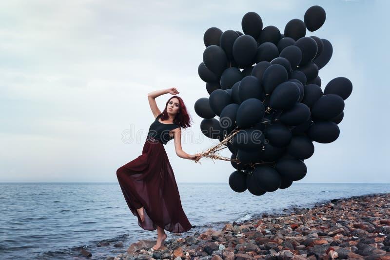 Όμορφο κορίτσι που περπατά με τα μαύρα μπαλόνια στοκ εικόνες
