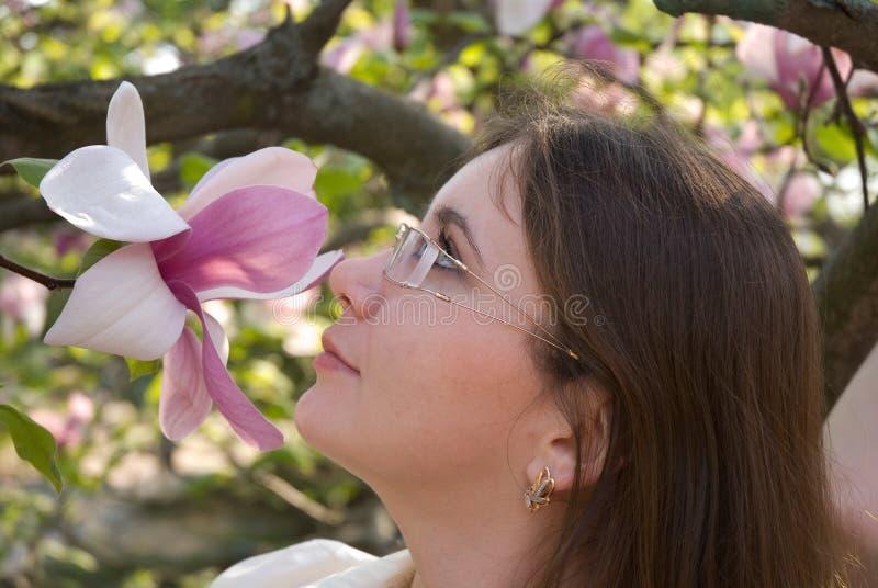 Όμορφο κορίτσι που ρουθουνίζει ένα ρόδινο λουλούδι magnolia στοκ φωτογραφίες