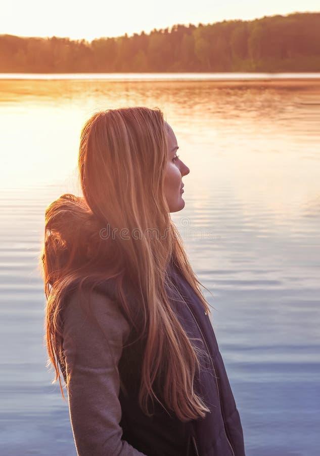 Όμορφο κορίτσι που στέκεται κοντά στο νερό υπαίθρια Χαριτωμένη μακρυμάλλης ξανθή λίμνη ηλιοβασιλέματος Νέα γυναίκα που σκέφτεται  στοκ φωτογραφία με δικαίωμα ελεύθερης χρήσης