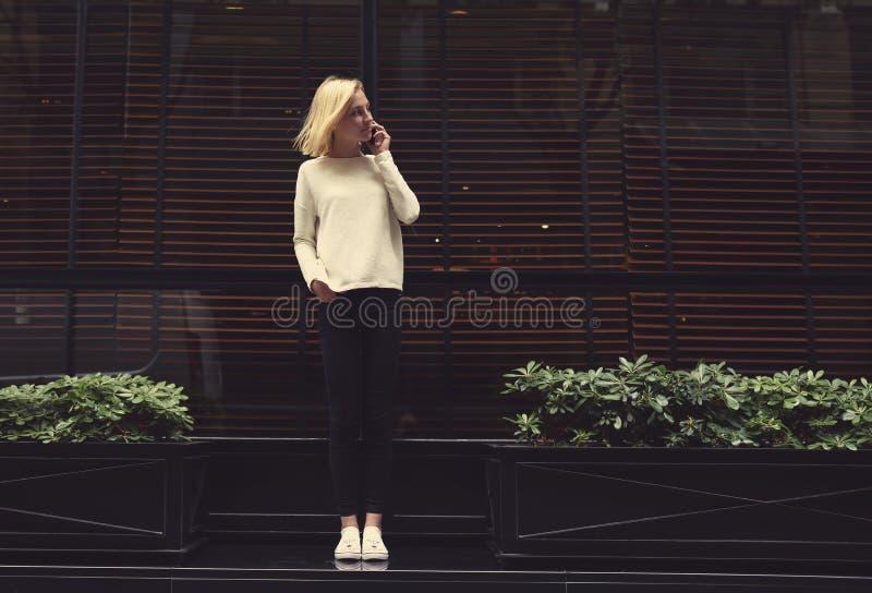 Όμορφο κορίτσι που στέκεται κοντά στο παράθυρο και έναν καφέ στο τηλέφωνο στοκ εικόνες με δικαίωμα ελεύθερης χρήσης