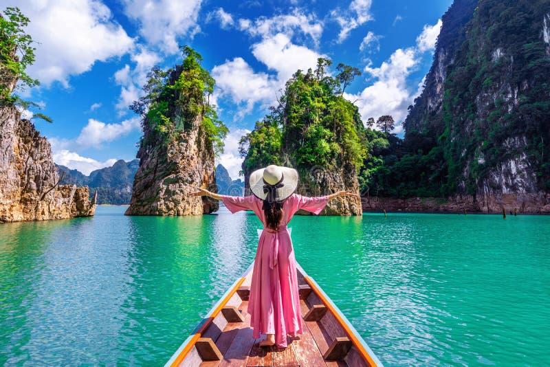 Όμορφο κορίτσι που στέκεται στη βάρκα και που κοιτάζει στα βουνά στο φράγμα Ratchaprapha στοκ εικόνες