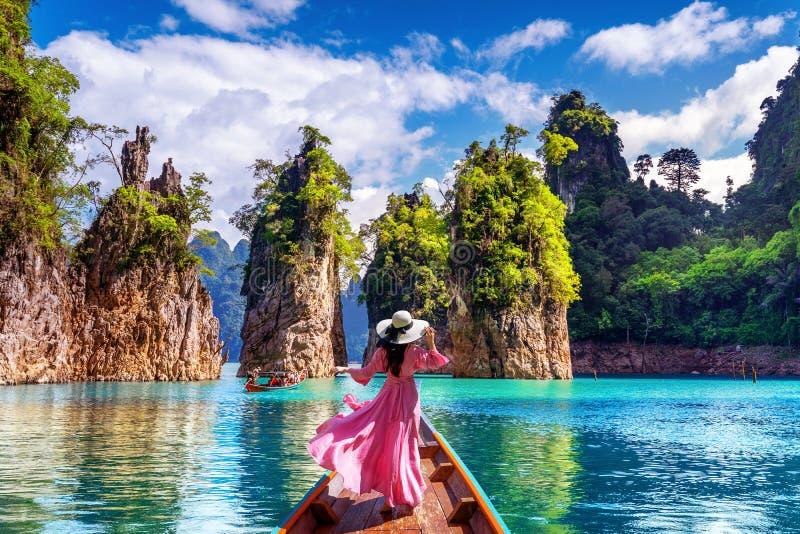 Όμορφο κορίτσι που στέκεται στη βάρκα και που κοιτάζει στα βουνά στο φράγμα Ratchaprapha στοκ φωτογραφία με δικαίωμα ελεύθερης χρήσης