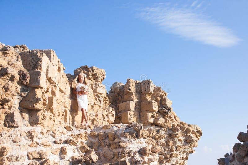 Όμορφο κορίτσι που στέκεται στον πετρώδη τοίχο στοκ εικόνες