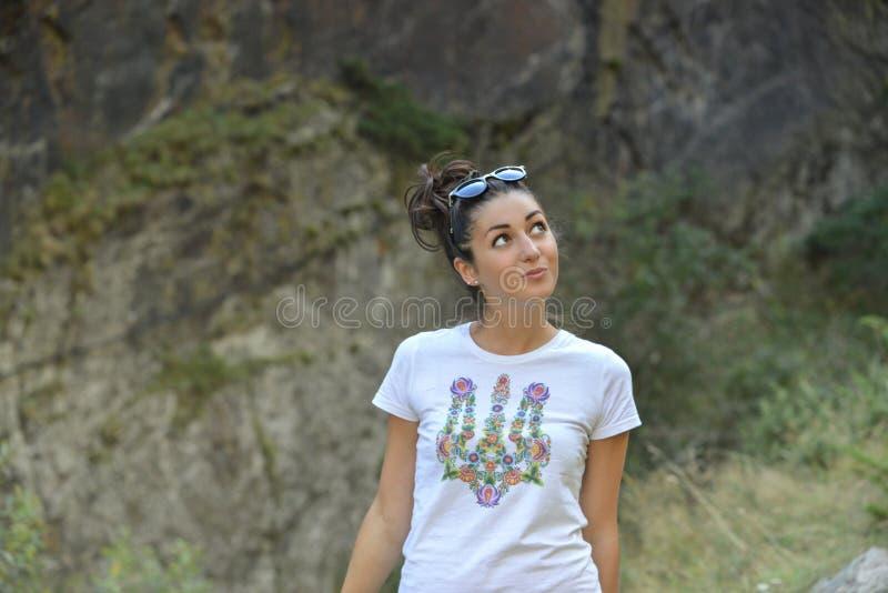 Όμορφο κορίτσι που στέκεται στο υπόβαθρο βουνών στοκ εικόνες