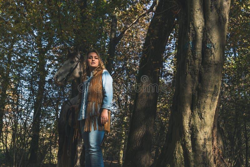 Όμορφο κορίτσι που υπερασπίζεται το γκρίζο άλογό της στοκ φωτογραφίες
