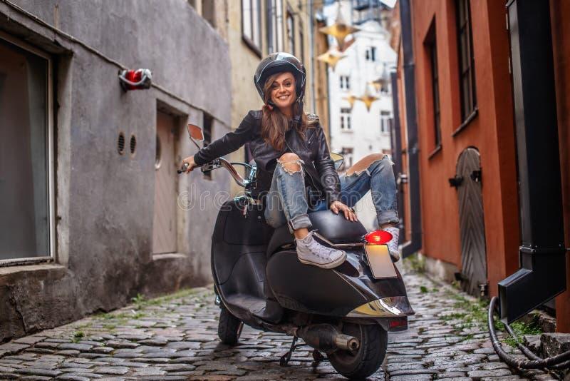 Όμορφο κορίτσι που φορά ένα σακάκι δέρματος και σχισμένα τζιν που κάθονται σε ένα μαύρο κλασικό μηχανικό δίκυκλο στην παλαιά στεν στοκ εικόνες