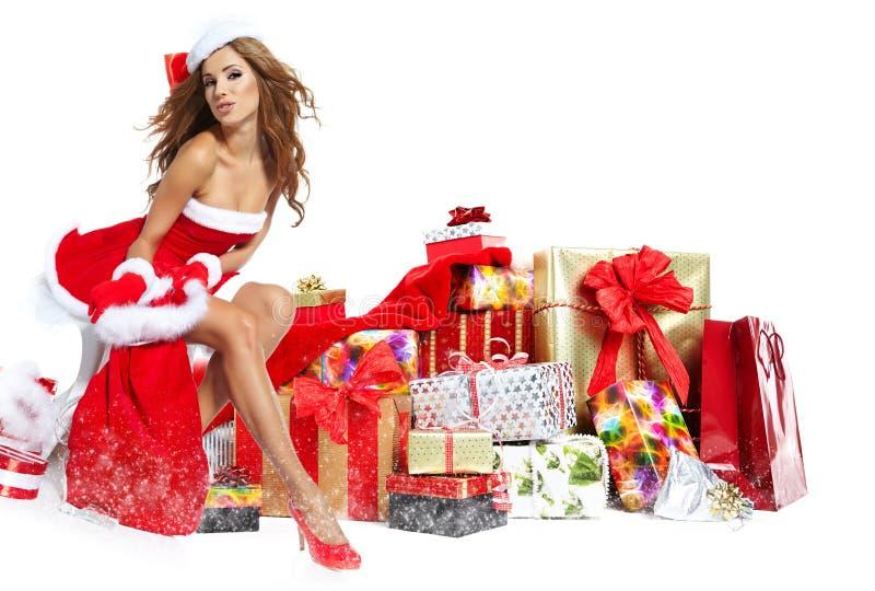 Όμορφο κορίτσι που φορά τα ενδύματα Άγιου Βασίλη με τα Χριστούγεννα γ στοκ φωτογραφία