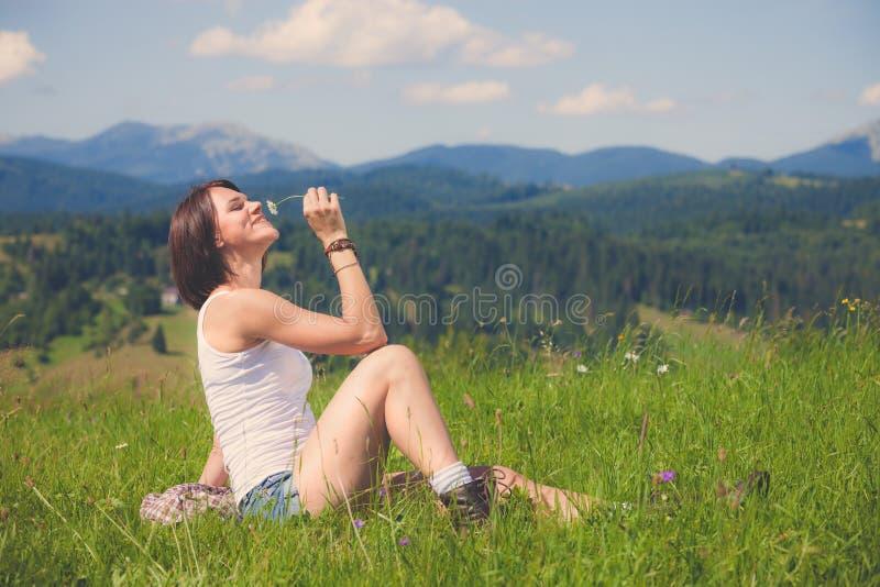 Όμορφο κορίτσι που χαμογελά και που βρίσκεται στον τομέα της πράσινης χλόης στοκ φωτογραφία με δικαίωμα ελεύθερης χρήσης