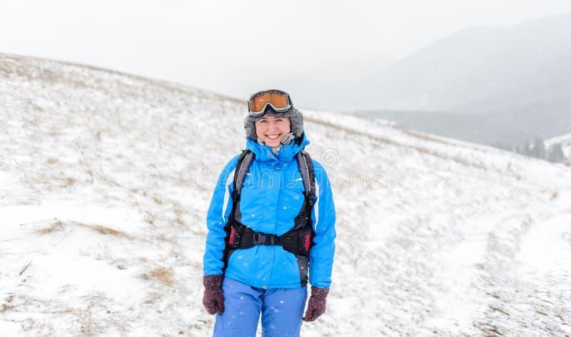 Όμορφο κορίτσι που χαμογελά πάνω από τα χιονισμένα βουνά στοκ εικόνα