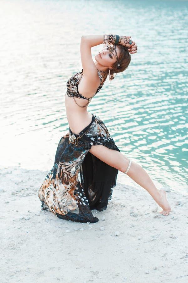 Όμορφο κορίτσι που χορεύει στο φυλετικό ύφος στην άσπρη παραλία άμμου πλησίον στοκ φωτογραφία με δικαίωμα ελεύθερης χρήσης