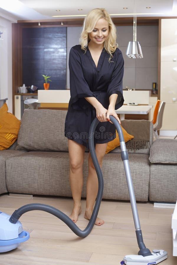 Όμορφο κορίτσι που χρησιμοποιεί την ηλεκτρική σκούπα στο σπίτι στοκ εικόνες