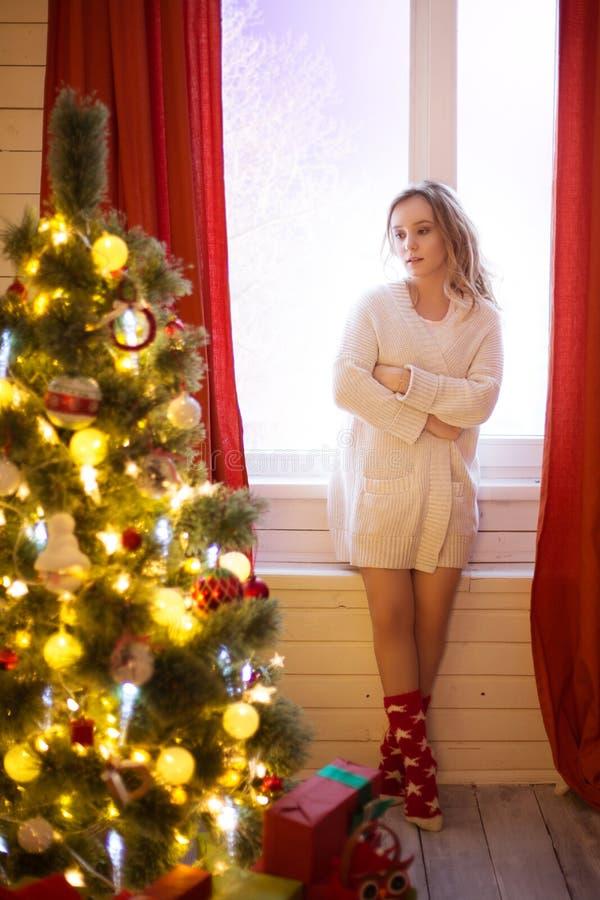 Όμορφο κορίτσι σε ένα θερμό πουλόβερ διακοπών με την παραμονή κοντά στο διακοσμημένο χριστουγεννιάτικο δέντρο στοκ φωτογραφία με δικαίωμα ελεύθερης χρήσης