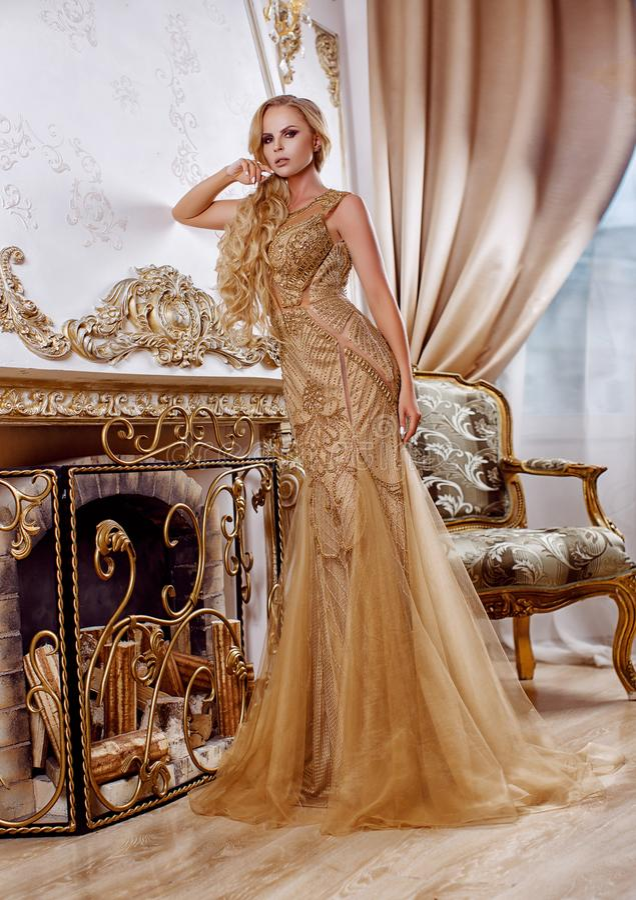 Όμορφο κορίτσι σε ένα μακρύ χρυσό φόρεμα στοκ εικόνα