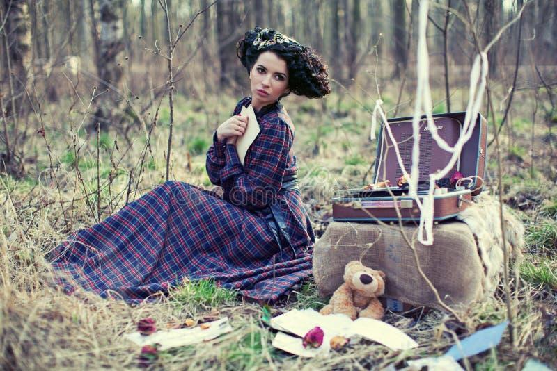 Όμορφο κορίτσι σε ένα φόρεμα καρό στα ξύλα στοκ φωτογραφία με δικαίωμα ελεύθερης χρήσης