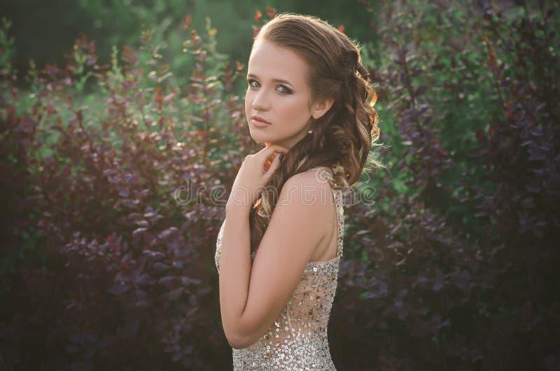 Όμορφο κορίτσι σε ένα φόρεμα που στέκεται σε ένα δάσος στο ηλιοβασίλεμα στοκ φωτογραφία με δικαίωμα ελεύθερης χρήσης