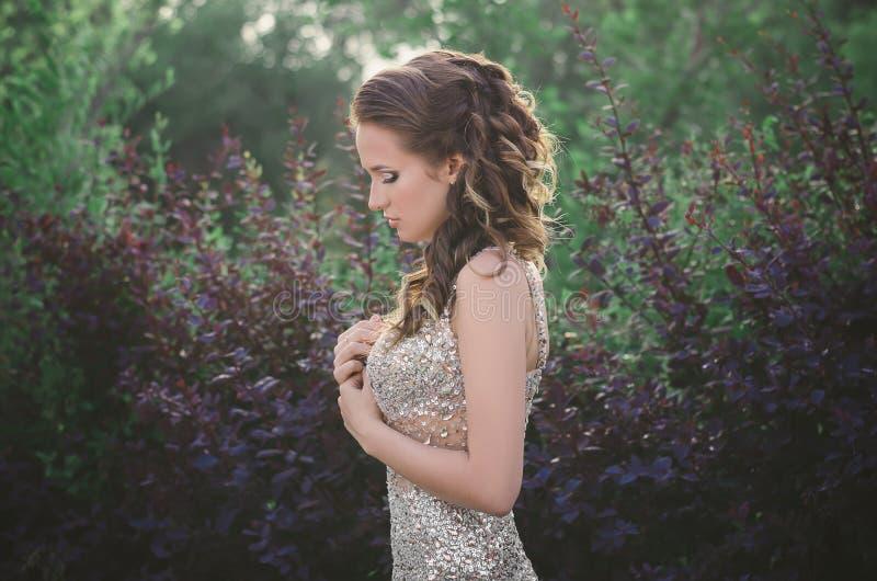 Όμορφο κορίτσι σε ένα φόρεμα που στέκεται σε ένα δάσος στο ηλιοβασίλεμα στοκ εικόνα με δικαίωμα ελεύθερης χρήσης