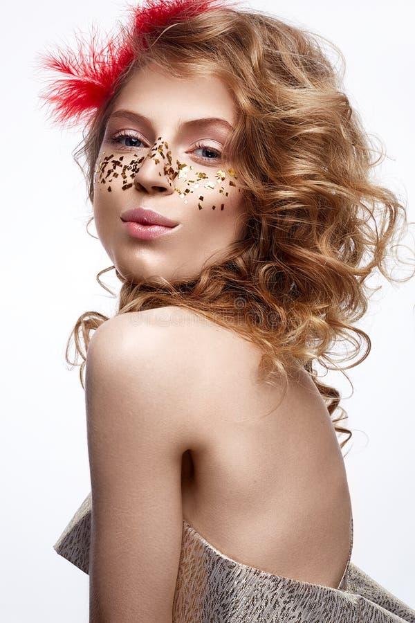Όμορφο κορίτσι σε ένα χρυσό φόρεμα με μια ευγενή σύνθεση Πρότυπο με τα κόκκινα φτερά στο κεφάλι και τις μπούκλες της Φωτογραφία δ στοκ εικόνα