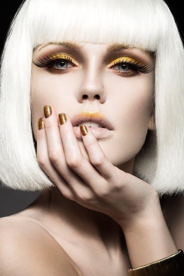 Όμορφο κορίτσι σε μια άσπρη περούκα, με το χρυσό makeup και τα καρφιά Εορταστική εικόνα Πρόσωπο ομορφιάς στοκ εικόνες