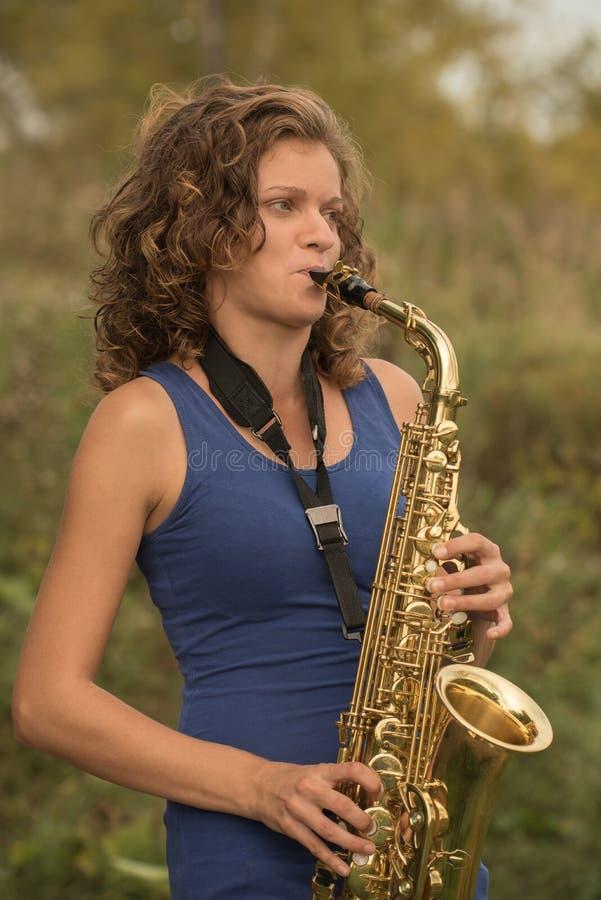 Όμορφο κορίτσι σε μια μπλε μπλούζα που παίζει το saxophone στο χρυσό ο στοκ εικόνες