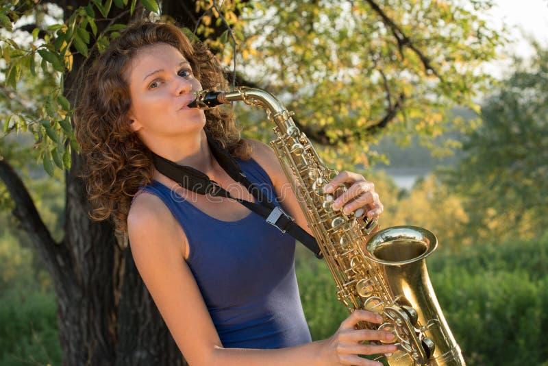 Όμορφο κορίτσι σε μια μπλε μπλούζα που παίζει το saxophone στο χρυσό ο στοκ φωτογραφία