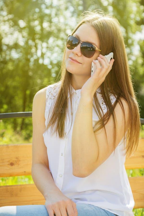 Όμορφο κορίτσι στα γυαλιά ηλίου με το κινητό τηλέφωνο στοκ φωτογραφίες με δικαίωμα ελεύθερης χρήσης