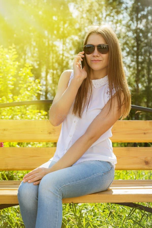 Όμορφο κορίτσι στα γυαλιά ηλίου με το κινητό τηλέφωνο στοκ φωτογραφία με δικαίωμα ελεύθερης χρήσης