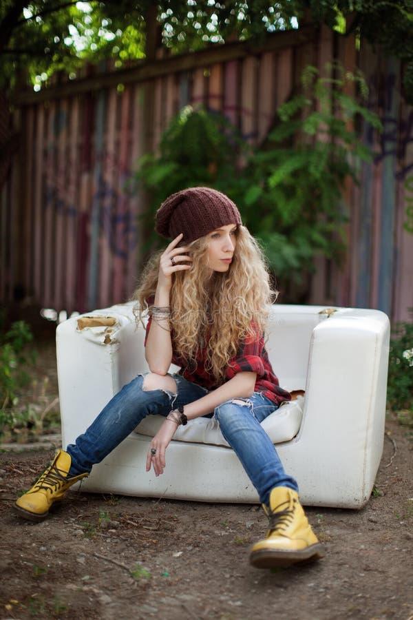 Όμορφο κορίτσι στα μοντέρνα ενδύματα σε έναν σπασμένο καναπέ στοκ φωτογραφία
