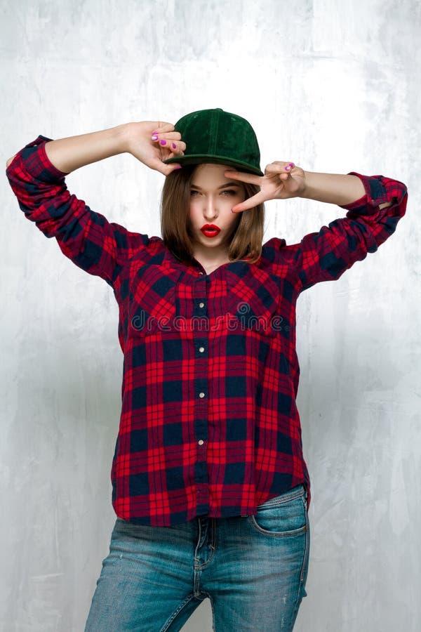 Όμορφο κορίτσι στα περιστασιακά ενδύματα και την πράσινη ΚΑΠ στοκ φωτογραφία