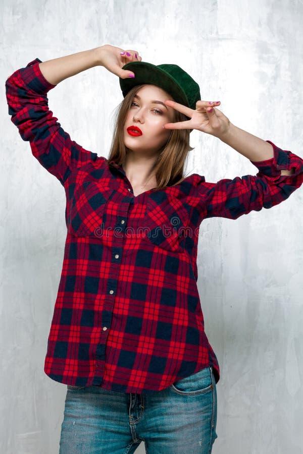 Όμορφο κορίτσι στα περιστασιακά ενδύματα και την πράσινη ΚΑΠ στοκ εικόνες
