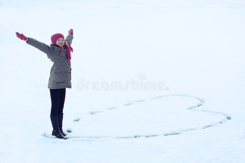 Όμορφο κορίτσι στα χειμερινά ενδύματα που επισύρουν την προσοχή την καρδιά στο χιόνι Ίχνος στο χιόνι στοκ φωτογραφίες με δικαίωμα ελεύθερης χρήσης