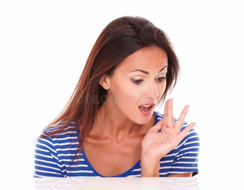 Όμορφο κορίτσι στην μπλε μπλούζα που ψιθυρίζει ένα μυστικό στοκ φωτογραφία με δικαίωμα ελεύθερης χρήσης