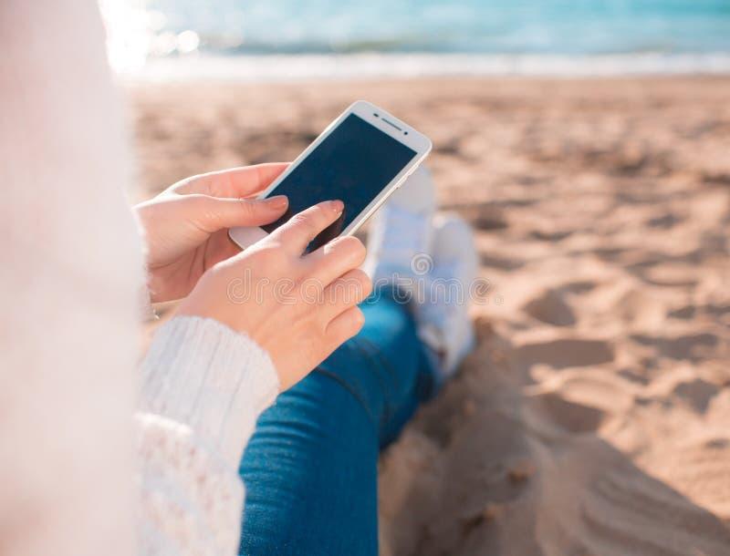 Όμορφο κορίτσι στην παραλία με το κινητό τηλέφωνο στοκ εικόνα
