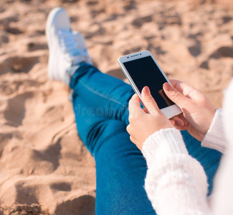 Όμορφο κορίτσι στην παραλία με το κινητό τηλέφωνο στοκ φωτογραφίες
