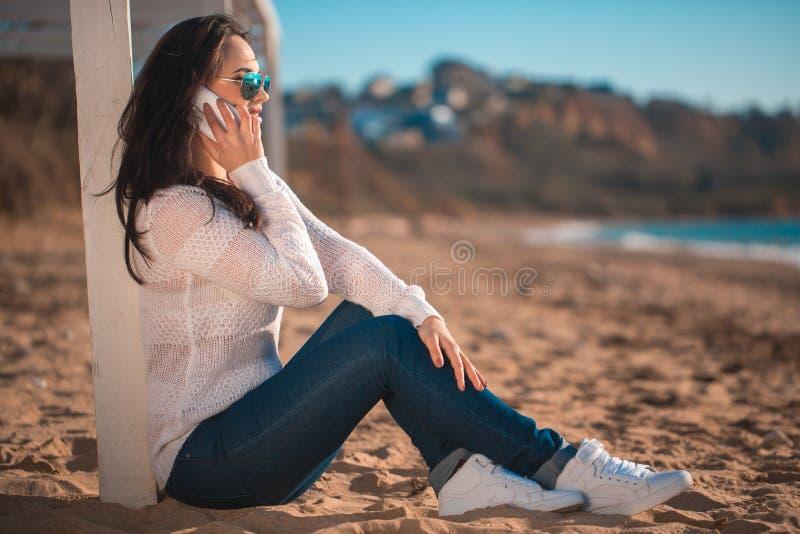 Όμορφο κορίτσι στην παραλία με το κινητό τηλέφωνο στοκ φωτογραφία με δικαίωμα ελεύθερης χρήσης