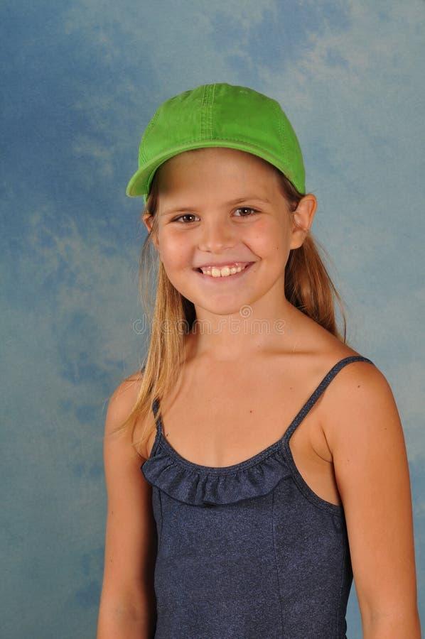 Όμορφο κορίτσι στην πράσινη ΚΑΠ στοκ εικόνα