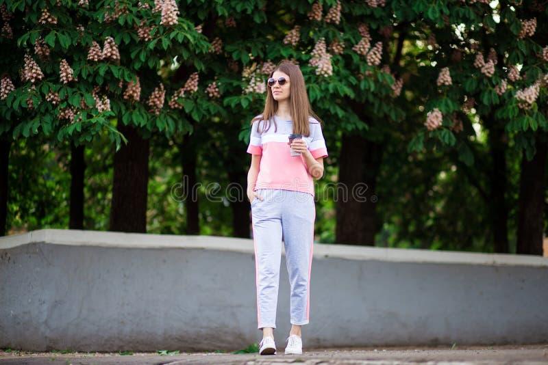 Όμορφο κορίτσι στον περίπατο γυαλιών ηλίου από τη θερινή οδό με τον καφέ στοκ φωτογραφίες