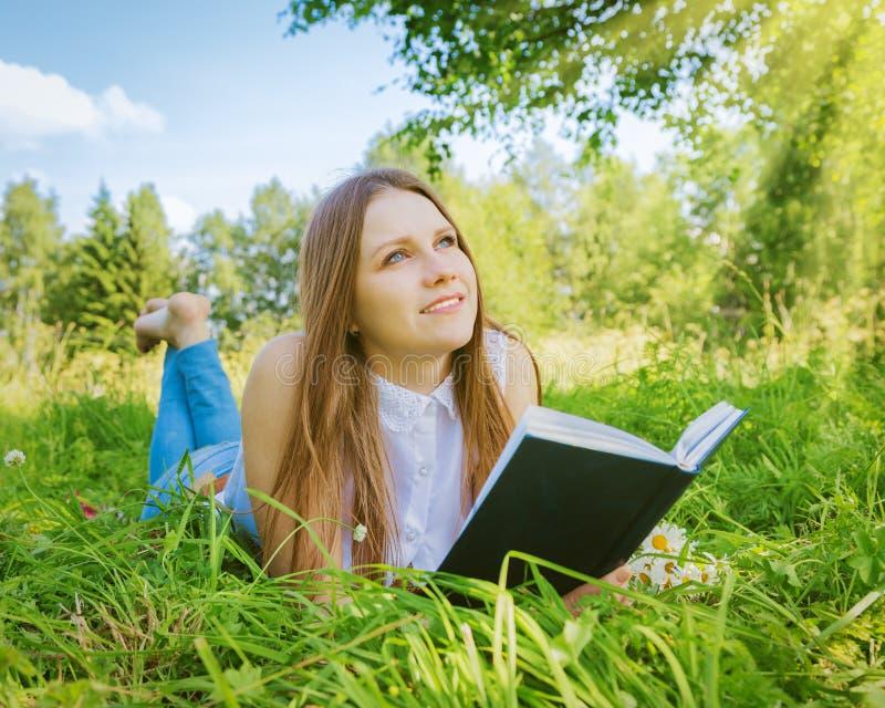 Όμορφο κορίτσι στο λιβάδι με ένα βιβλίο στοκ φωτογραφία με δικαίωμα ελεύθερης χρήσης