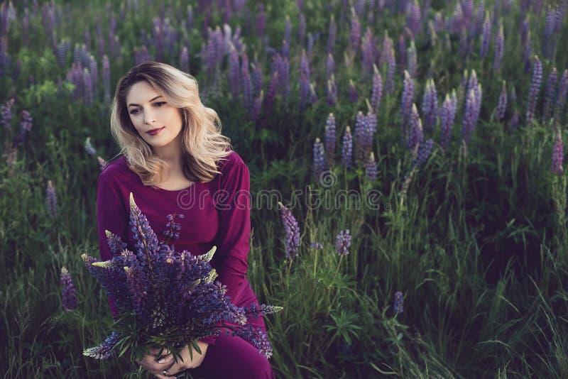 Όμορφο κορίτσι στο ιώδες φόρεμα που κρατά ένα lupine στο ηλιοβασίλεμα στον τομέα Η έννοια της φύσης και του ειδυλλίου στοκ εικόνες