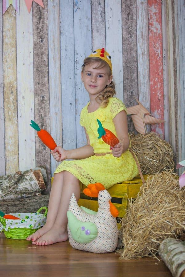 Όμορφο κορίτσι στο κίτρινο φόρεμα, που παίζει με το καρότο στοκ εικόνα