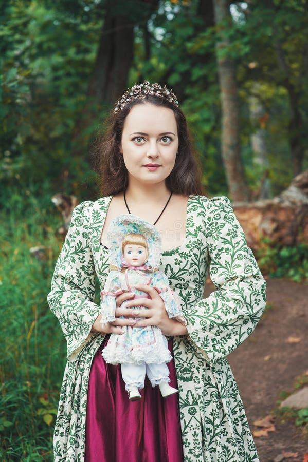 Όμορφο κορίτσι στο μακρύ μεσαιωνικό φόρεμα με την εκλεκτής ποιότητας κούκλα στοκ φωτογραφίες με δικαίωμα ελεύθερης χρήσης