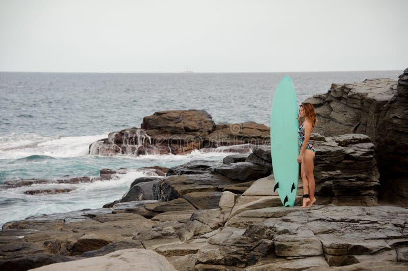 Όμορφο κορίτσι στο πολυ χρωματισμένο μαγιό που στέκεται με την κυματωγή στην παραλία βράχου στοκ εικόνα