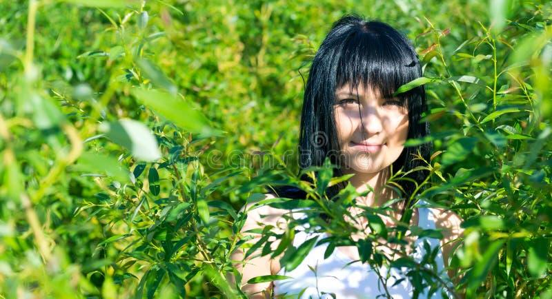 Όμορφο κορίτσι στο πράσινο φύλλωμα στοκ εικόνα με δικαίωμα ελεύθερης χρήσης