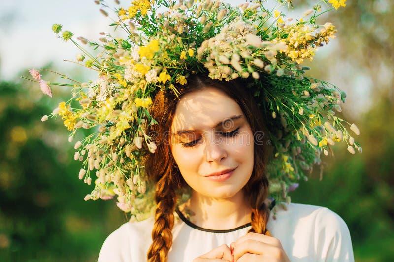 Όμορφο κορίτσι στο στεφάνι των λουλουδιών στο λιβάδι την ηλιόλουστη ημέρα Πορτρέτο της νέας όμορφης γυναίκας που φορά ένα στεφάνι στοκ φωτογραφία με δικαίωμα ελεύθερης χρήσης