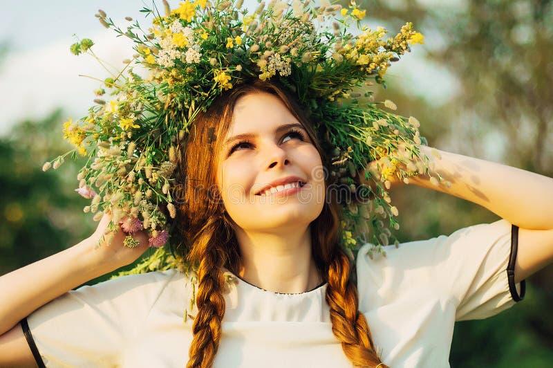 Όμορφο κορίτσι στο στεφάνι των λουλουδιών στο λιβάδι την ηλιόλουστη ημέρα Πορτρέτο της νέας όμορφης γυναίκας που φορά ένα στεφάνι στοκ εικόνα