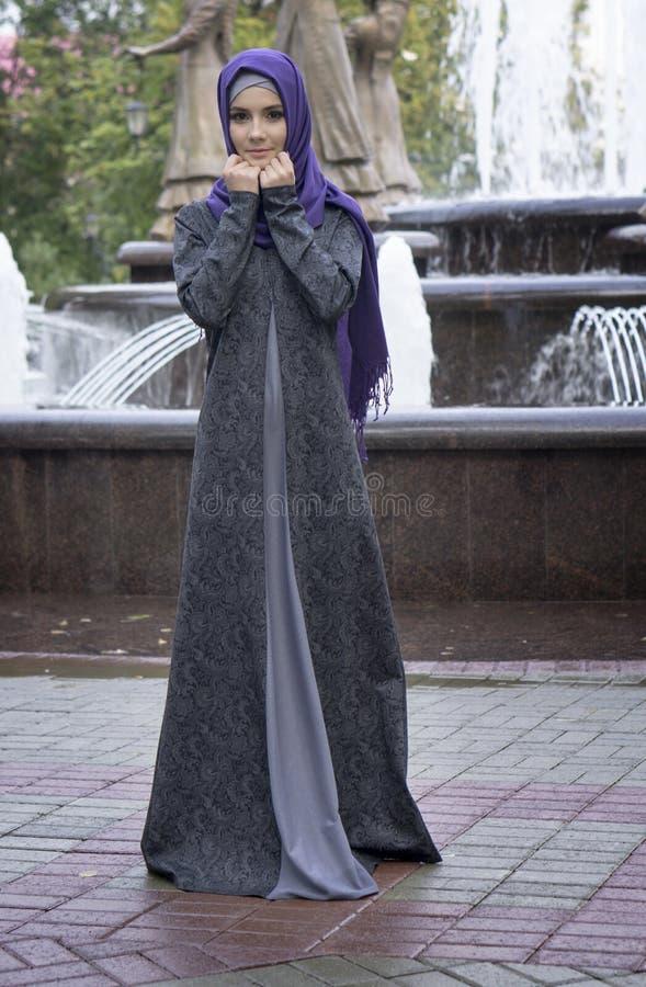 Όμορφο κορίτσι στο σύγχρονο μουσουλμανικό φόρεμα σε ένα υπόβαθρο μιας πηγής στοκ εικόνα