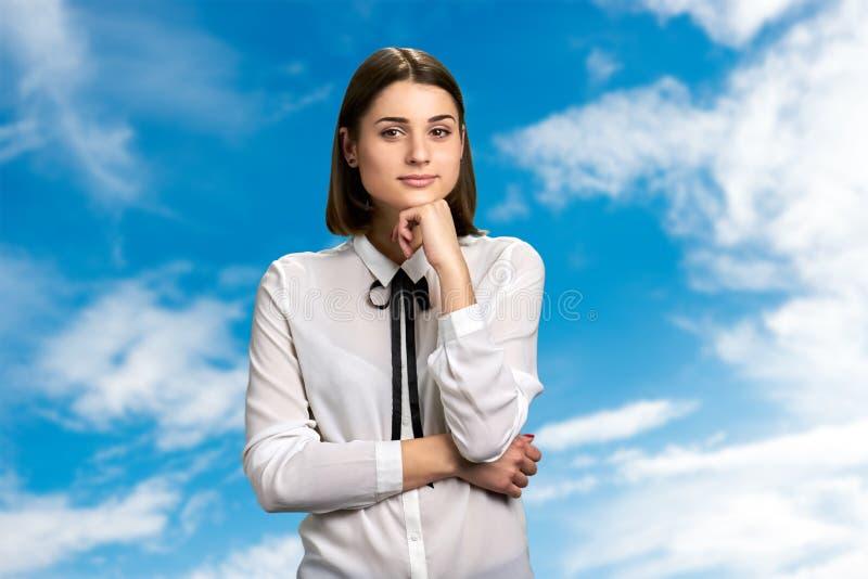 Όμορφο κορίτσι στο υπόβαθρο μπλε ουρανού στοκ φωτογραφίες
