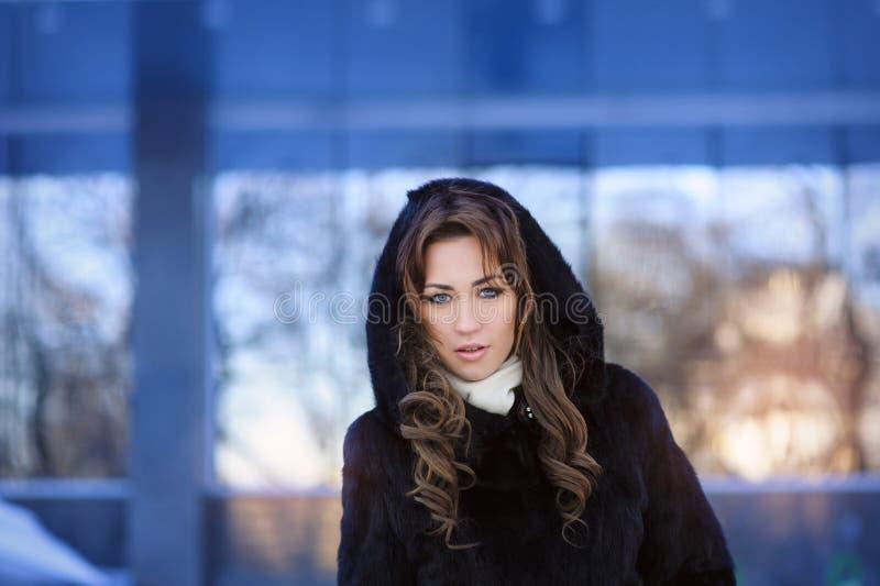 Όμορφο κορίτσι στο χειμερινό παλτό με την κουκούλα στοκ φωτογραφία