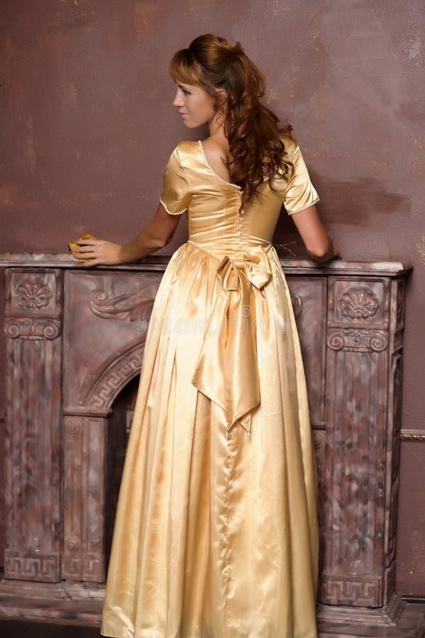 Όμορφο κορίτσι στο χρυσό φόρεμα στοκ εικόνες